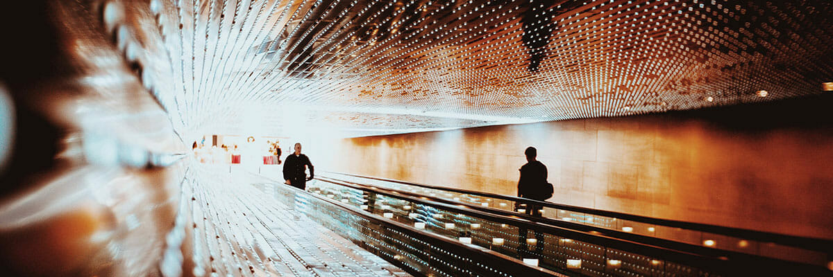 Two people riding a moving sidewalk into a bright white void to represent transformation