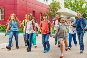 Happy kids with rucksacks walking leaving school