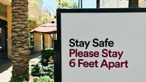 sign cautioning people to remain six feet apart at a shopping mall or retail space for COVID-19 precautions